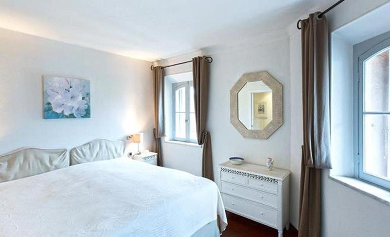 White themed double bedroom with brown curtains for the windows in a Cannes apartment in Le Suquet.