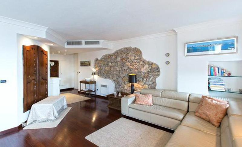 Spacious living room with a stone wall, wooden floor and leather couch in a Cannes rental apartment next to convention centre