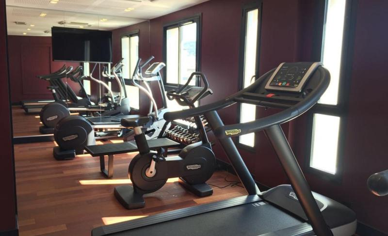 Running, cycling and cross trainer machines in a gym with weights in a Cannes hotel