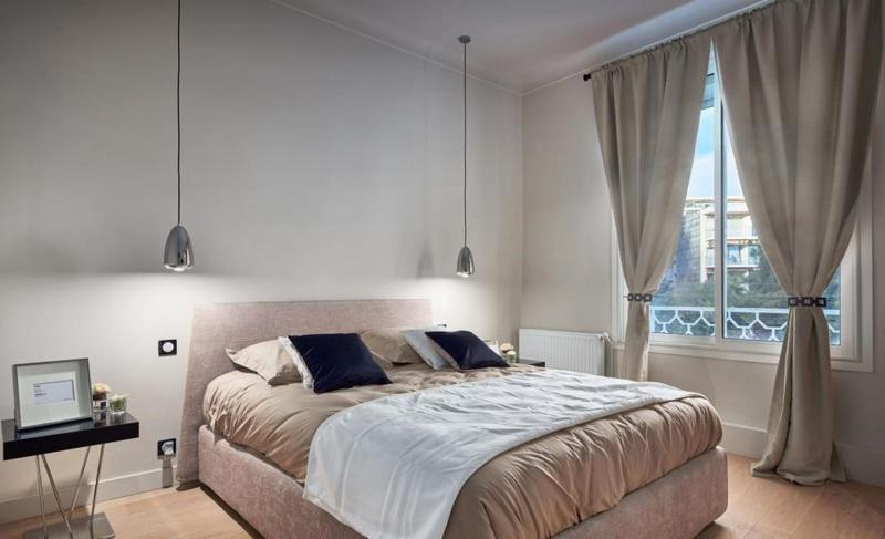 Salt coloured bed and beige coloured mattress with wooden flooring in a double bedroom with an exterior window