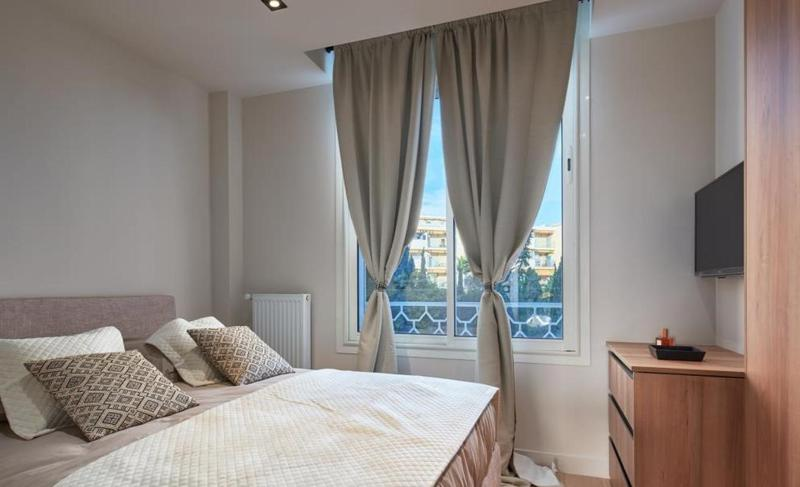 Double bedroom with white pillows and blanket and a view of Cannes from the window