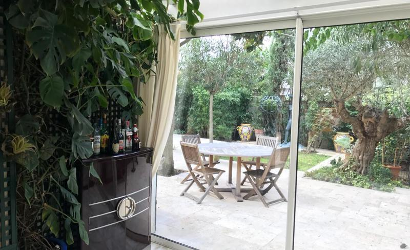 Mini bar with alcohol next to the plant and view of the garden with trees, plants and furniture in Cannes