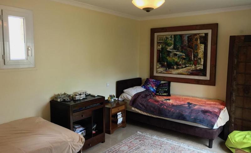 2 single beds placed separately in a bedroom with wall paintings and side tables in Cannes