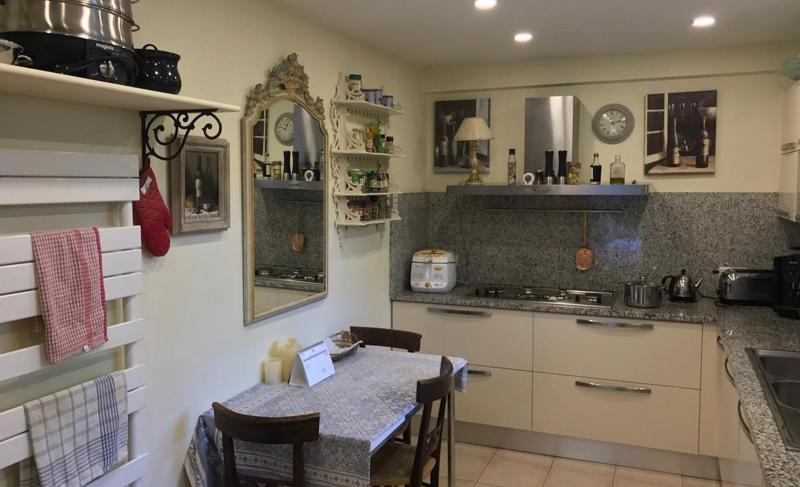 Kitchen with a stove, coffee maker, toaster, shelves, drawers and a 3 person breakfast table in Cannes