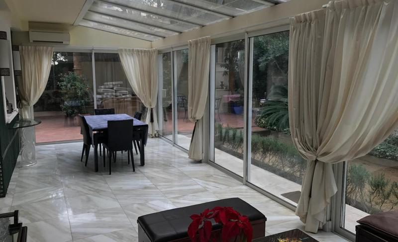Conference room with table, furniture and pleasant garden view through glass walls in a Cannes rental villa for groups.