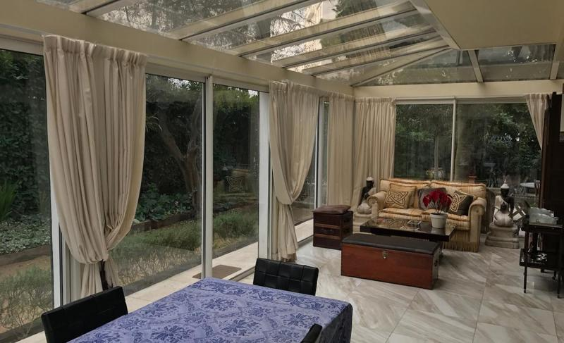 Relaxing lounge with elegant couch, dining table and beige curtains for glass walls in Cannes event villa for rent.