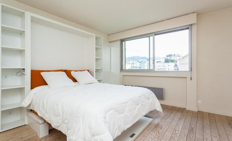 Double orange bed with a white blanket in a studio apartment with a window in Cannes near to Convention centre