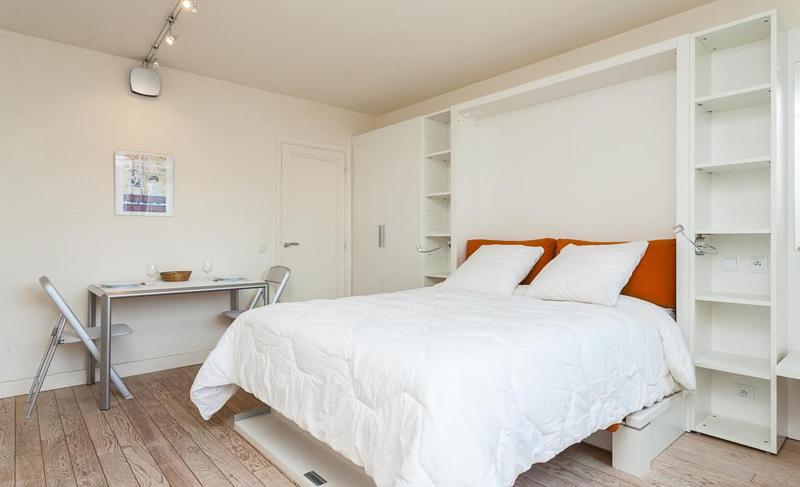 Double bed with a white blanket and a desk table and 2 chairs in Cannes
