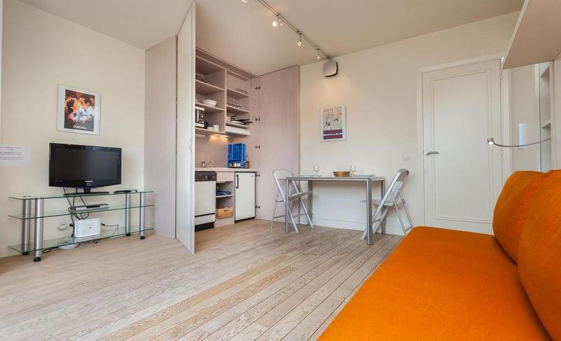 Orange couch facing a flat screen tv in the living room with an open kitchen in a Cannes studio accommodation