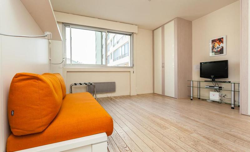 Orange pull out couch, a flat screen tv and a wardrobe in the corner of a Cannes studio apartment