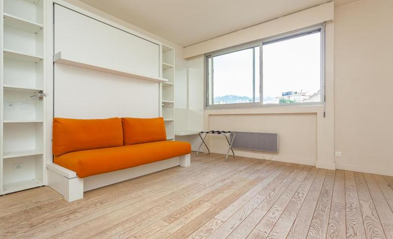 Pull out couch in a living room with wooden floor and a window with Cannes view