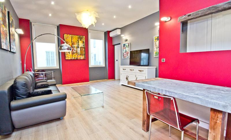 Red and grey interiors in the living room of an artistic Cannes event rental apartment with paintings, couch set and a tv