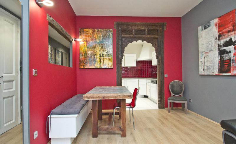 Grey and red painted walls in a 1 bedroom rental apartment with wall paintings and a wooden table