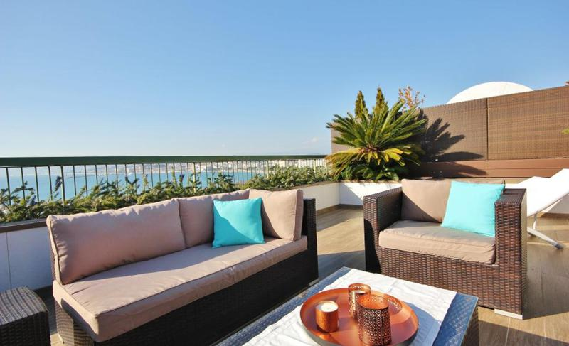 Couch set on the outdoor deck with green plants of a sea facing corporate Cannes penthouse