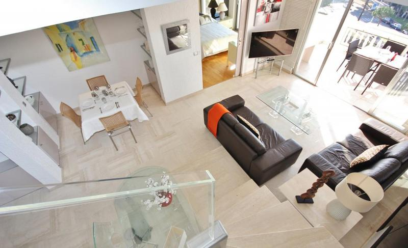 Top view of a furnished living room with an open sliding glass door leading to a terrace offering Cannes street views