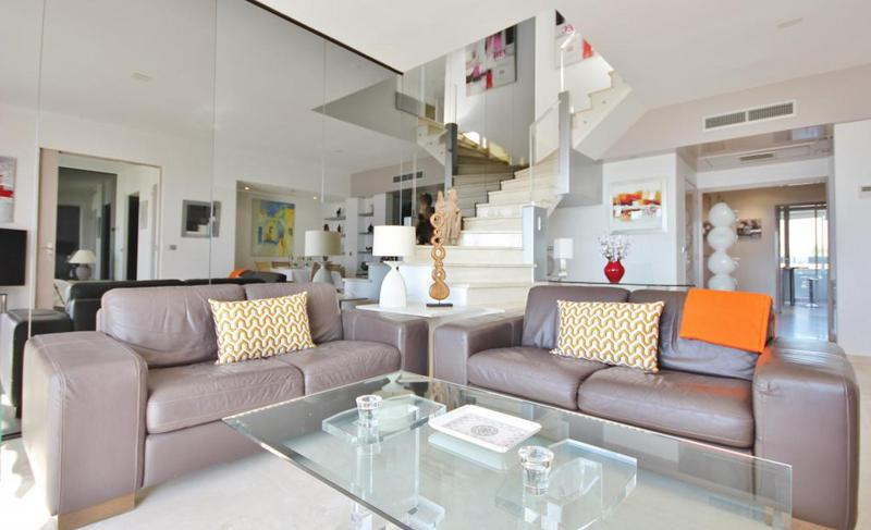 Living room with leather couches, a glass wall and cream coloured interiors in Cannes rental apartment