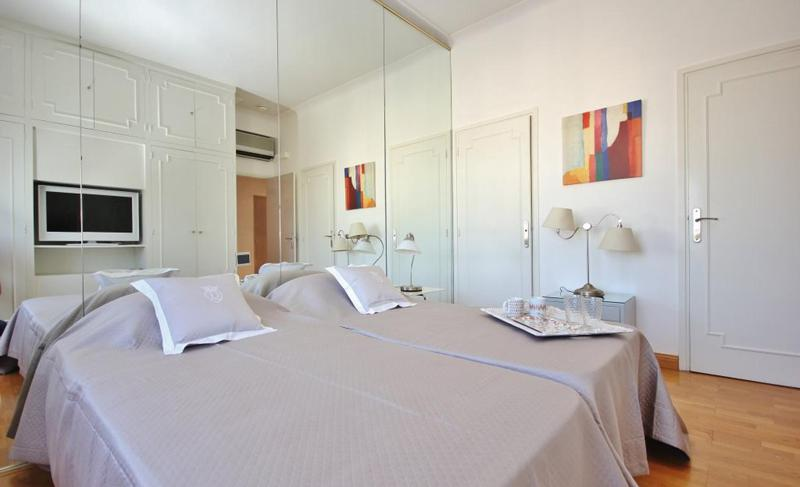 2 Single beds in a room with a mirror wall and wooden floor in Cannes