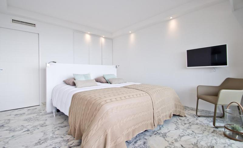 Marble flooring in a bedroom with white interiors and double bed with a beige coloured blanket and a mounted tv