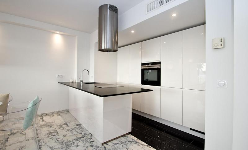 White open kitchen with black slab and kitchen hood