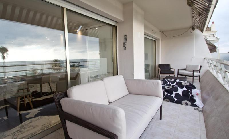 Outdoor couch with white cushions and chairs in a Cannes apartment by the sea