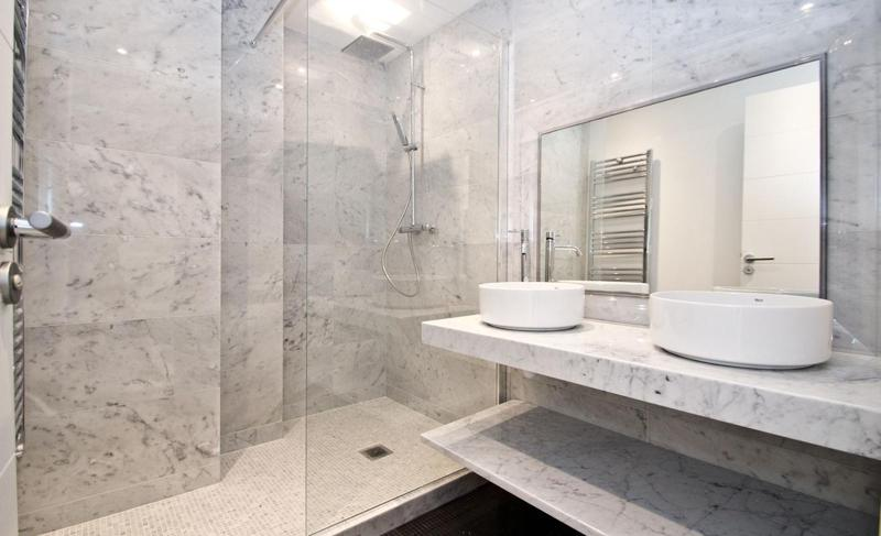 Bathroom with marble walls, separate shower and sinks
