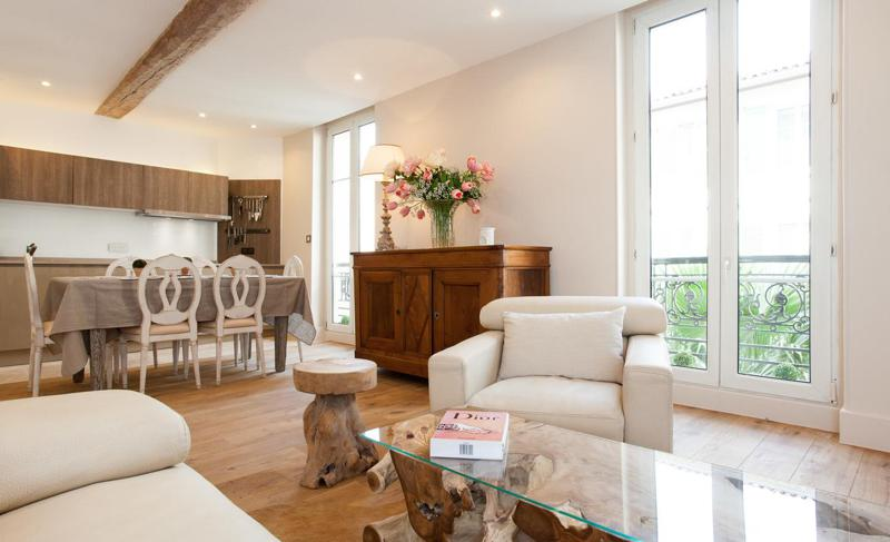 Wooden furnished living room with an open kitchen and dining table in a Cannes group apartment