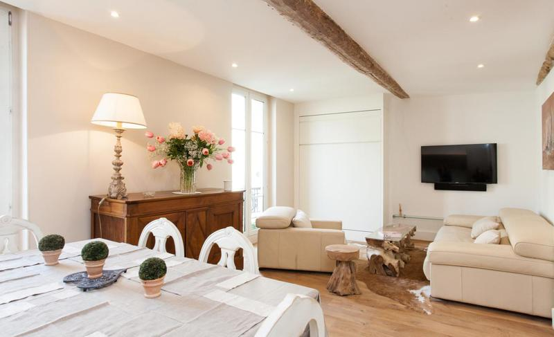 Living room with cream interiors, flat screen tv, cream sofa set, white dining table for group accommodation in Cannes