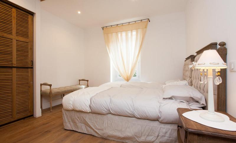2 single beds in a room with fitted wooden closet and a window in Palais centre