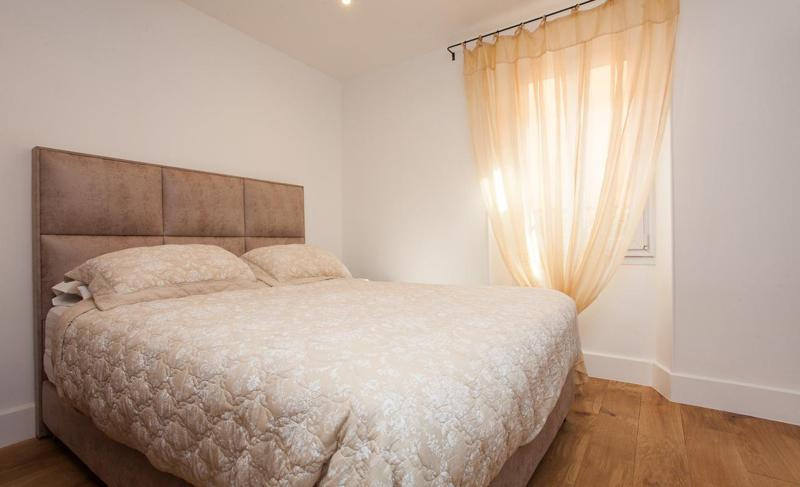 Beige coloured double bed and blanket in a room with white walls and golden window curtain