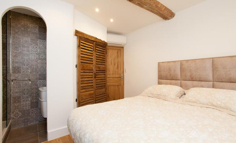 Double bedroom with a fitted wooden closet and attached bathroom in Cannes central accommodation