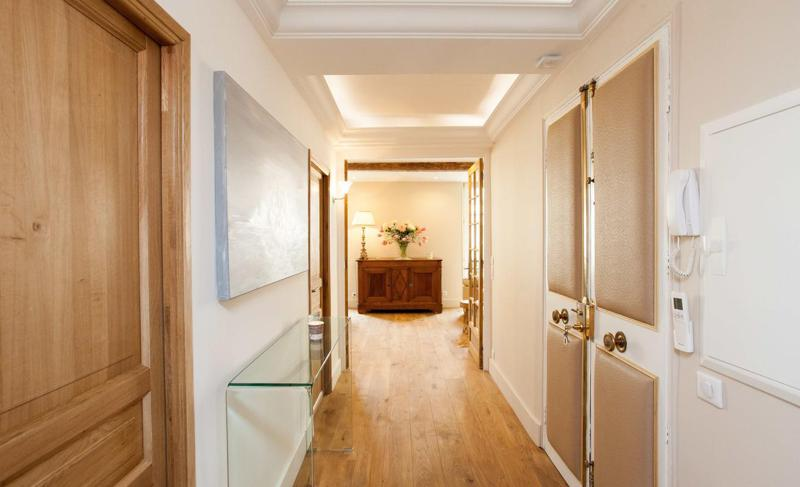 Entrance hallway with wooden floor and doors on both sides, a wall painting and a cabinet at the end in Central Cannes