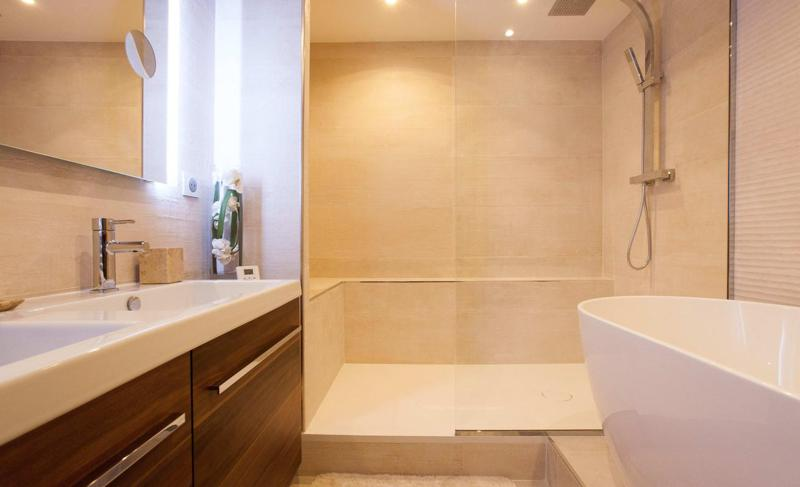 Bathroom with a white bathtub, a mirror and a separate shower