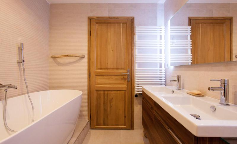 White bathtub and 2 sinks in a bathroom with wooden door