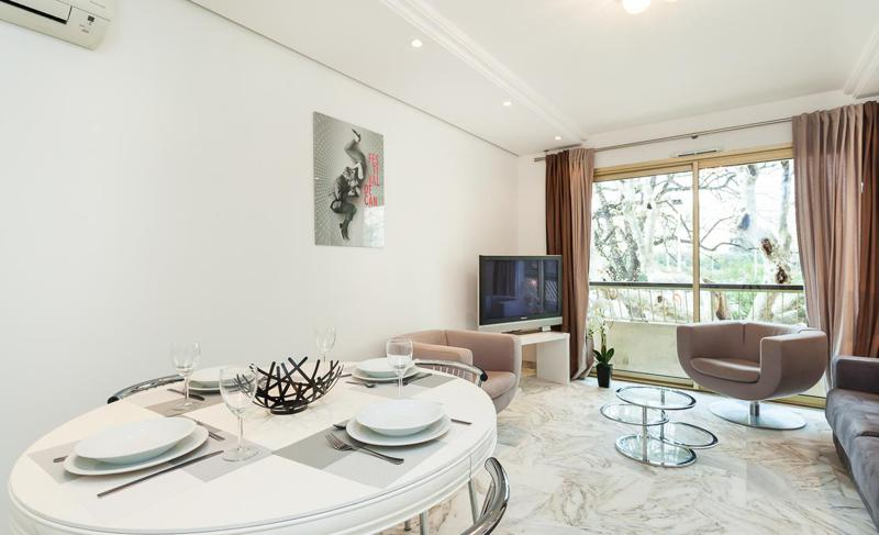 Marble floored living room with a flat screen tv, white dinner table and a private balcony in Cannes group accommodation