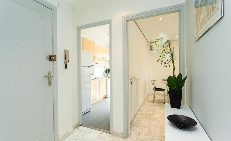 Cannes group apartment´s entrance with one door leading to kitchen and the other one to the living room
