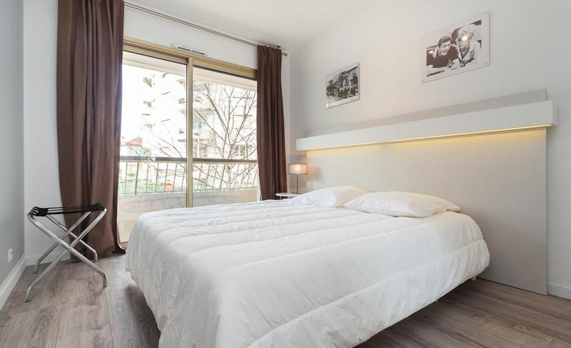Double bedroom with white interior and blanket, and a balcony offering views of surroundings in a Cannes rental apartment