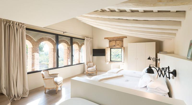 2 single beds and chairs in a bedroom with closet, tv and windows with views of green landscapes in a Barcelona group villa