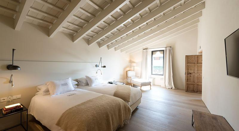 2 single beds in a bedroom with natural light, wooden closet and slanted roof in Barcelona