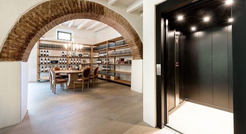 Wine cellar and a round wooden table with chairs and elevator in the living room of a Barcelona group party Villa