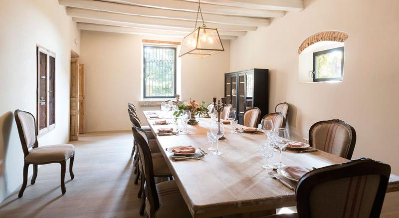 Dining table set with plates, glasses, napkins and sileverware in a Barcelona rental villa