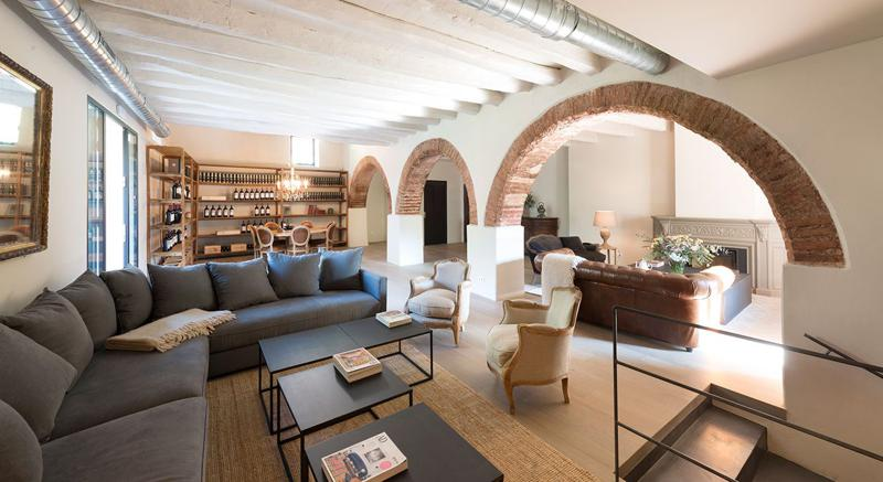 Living room with 2 separate seating areas, a wine cellar and a fireplace in Barcelona group party villa