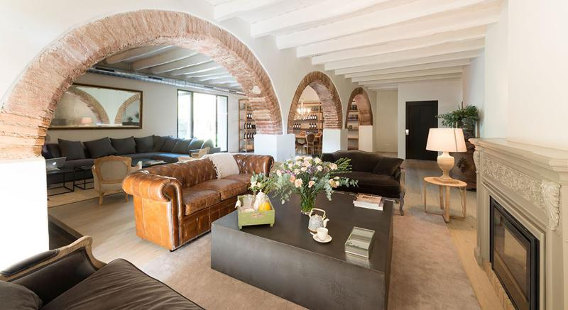 Living room with a couch, a fireplace and a tunnel-shaped wall separating another seating area in Barcelona event villa