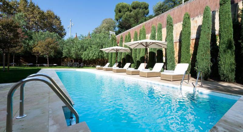 Swimming pool and garden with lounge chairs and umbrellas in a Barcelona MWC group villa