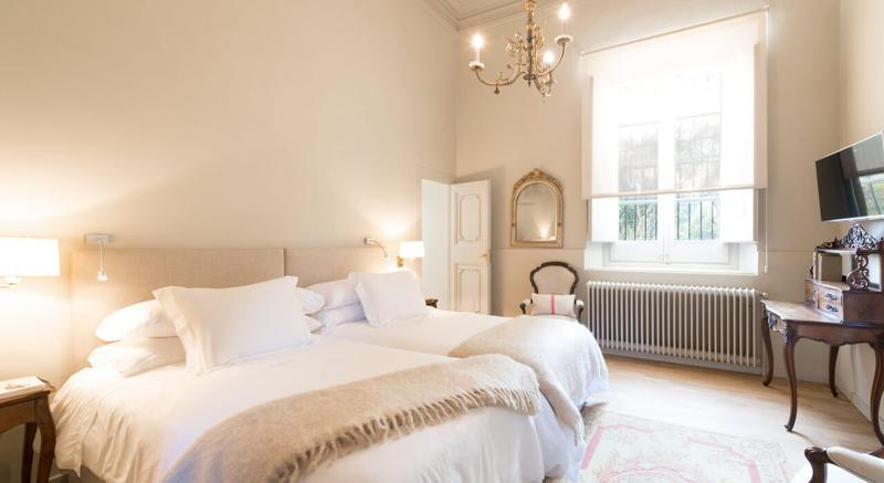 Bedroom with 2 single beds, a candle chandelier hanging from the ceiling and a window in Barcelona