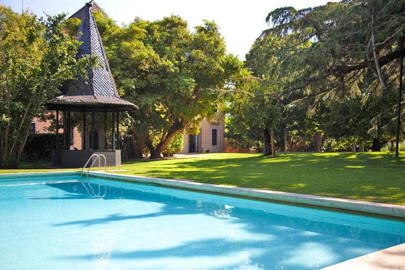 Swimming pool in a garden with palm trees and a hut in a Barcelona rental villa