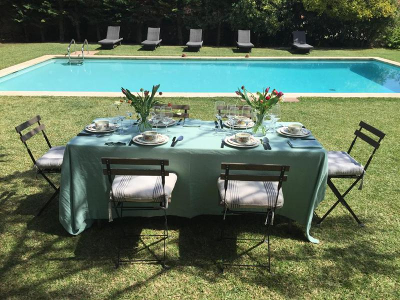 Swimming pool with lounge chairs on one side and dinner table on the other in Barcelona group party villa