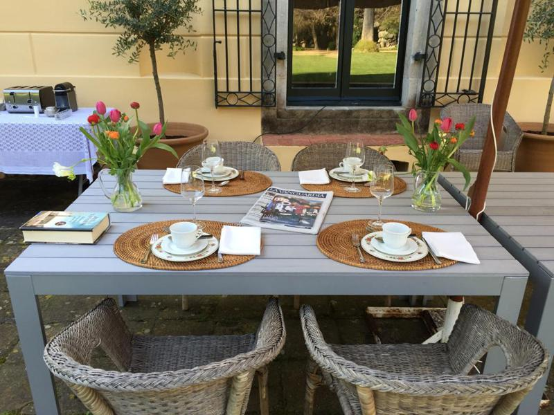 Book, newspaper and teacups on a table in the garden of a Barcelona villa