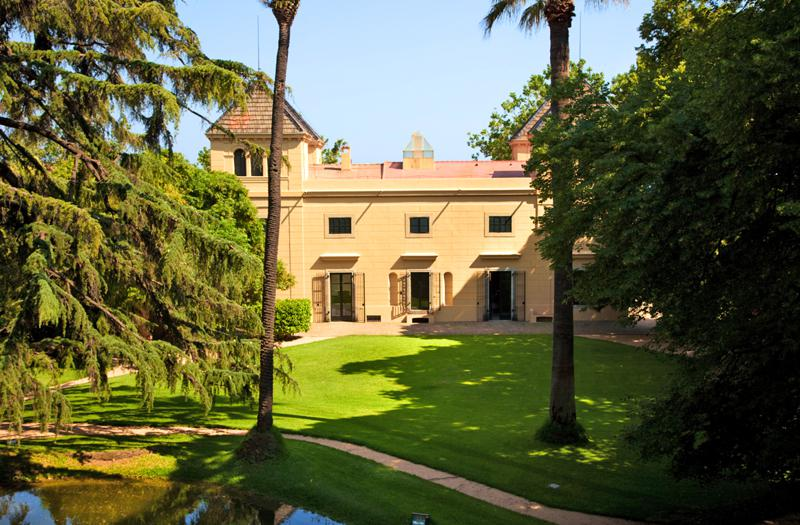 Driveway in front and a walking path in the garden of a yellow painted villa in Barcelona