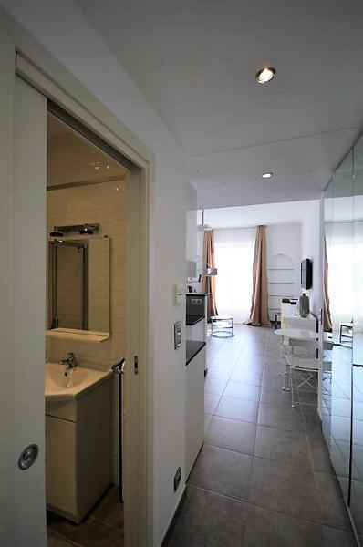 View of bathroom with a sink and the a living room with 2 chairs and at table from the lobby of an apartment