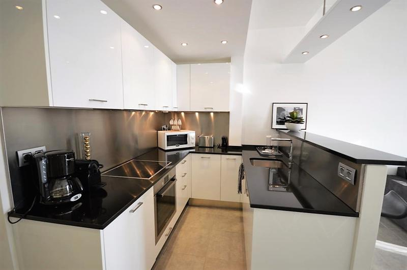 White themed kitchen with black countertops, a coffee maker, a microwave, a toaster, an oven and induction stove in Cannes